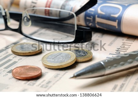 Euro money coins, glasses and ball pen on a financial report - stock photo