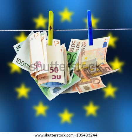 Euro money dries on the wire with Euro flag in background - stock photo