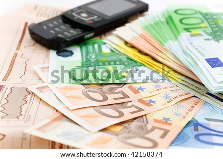 euro notes and black mobile phone on a financial newspaper. closeup. small GRIP - stock photo