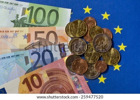 Euro notes and coins on EU flag - stock photo
