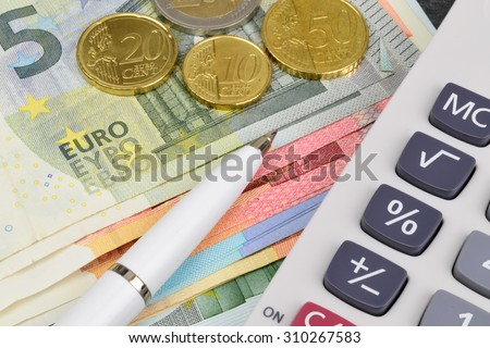 Euro notes and coins, with a calculator and pen.