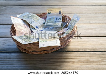 euro notes 5 to 10 in a wicker basket - stock photo