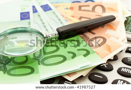 Euro Notes with calculator and magnifier. Closeup