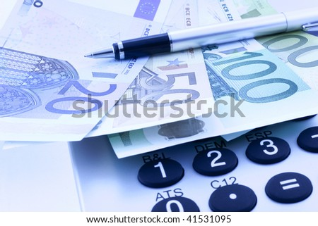 Euro notes with calculator and pen in blue. closeup. small GRIP - stock photo