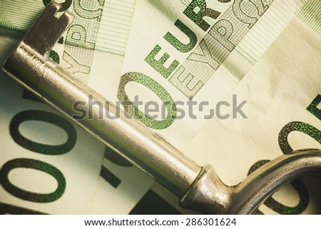 Euro one hundred banknotes and metal key, symbolically presenting success.  - stock photo