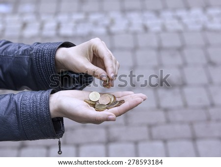 Euro small change in the hands of women. - stock photo