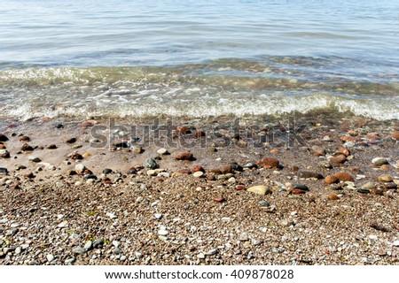 Europe, Baltic, Latvia.The transparent wave washes beautiful pebble on the coast of the Baltic Sea. - stock photo