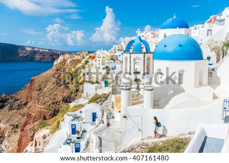 Europe, Greek Islands, Greece, Santorini travel tourist vacation destination: City of Oia. Woman on holidays walking on stairs visiting the famous white village by mediterranean sea and blue domes.  - stock photo
