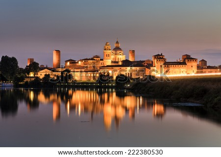 Europe Italy Mantova-Mantua ancient castle at the river reflecting in still waters at sunset highly illuminated by lights - stock photo