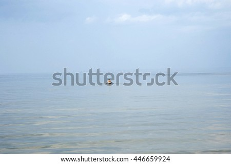 Europe. Latvia. The man enters water on the beach of Jurmala during a calm in the Gulf of Riga.