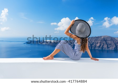 Europe summer vacation travel cruise destination luxury living woman relaxing on outdoor terrace looking at view of Mediterranean Sea and Santorini Oia. Elegant tourist lady in fashion beachwear. - stock photo