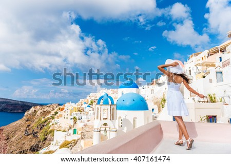 Europe tourist travel woman in Oia, Santorini, Greece. Happy young woman looking at famous blue dome church landmark destination. Beautiful girl in white dress on visiting the Greek island. - stock photo