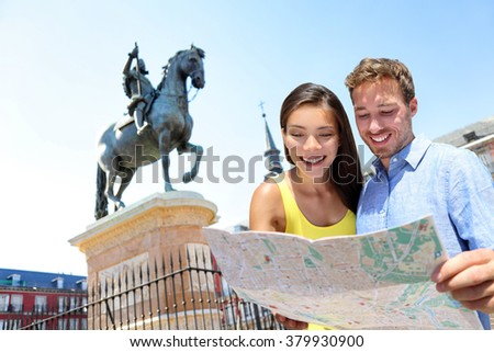 Europe travel couple looking at map in Madrid. Two happy beautiful young adults looking for directions during european summer vacations in Plaza Mayor, Madrid, Spain. - stock photo