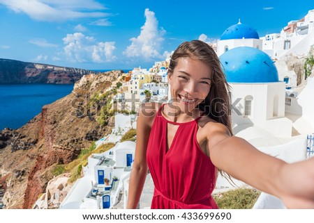 Europe travel selfie Asian woman in Oia village, Santorini. Cute happy smiling tourist girl taking self-portrait picture with smartphone during summer vacation in famous European destination, Greece. - stock photo
