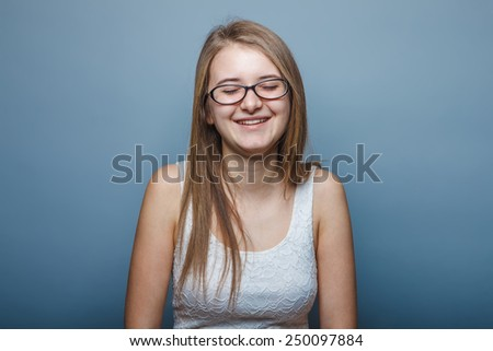 European appearance blonde girl with glasses closed her eyes laughing on a gray background, joy