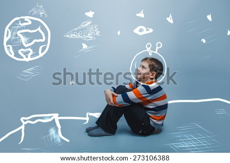 European appearance boy ten years dreaming sitting thinking on a gray background - stock photo