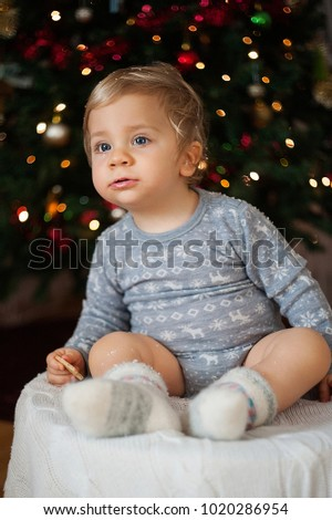 European baby in woolen body and woolen socks on the background of a Christmas tree
