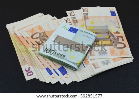 European banknotes on black background. Euro money with silver metal clips