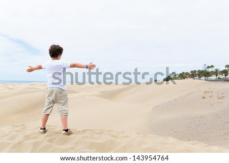 European boy stands on the sandy bottom of the outstretched hands - stock photo
