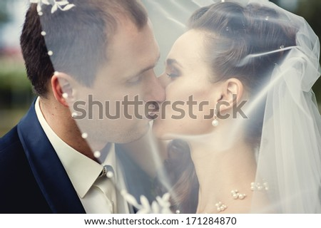 European bride and groom kissing in the park. Wedding shot of elegant bride and groom posing together outdoors on a wedding day. wedding dress. Bridal wedding bouquet of flowers.