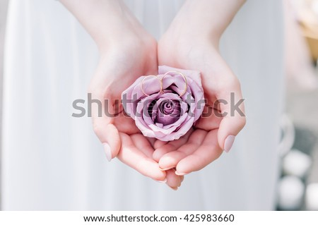 European bride holding a rose and wedding rings on her hands.