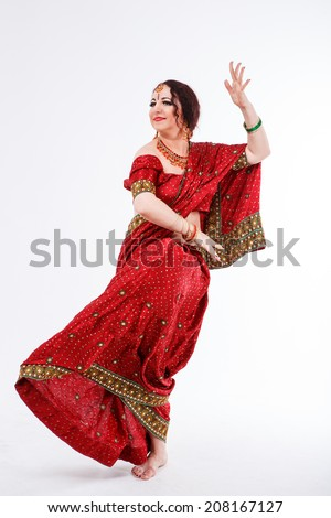 european brunette girl in red indian saree dancing with her hands and flying skirt in studio on gray background