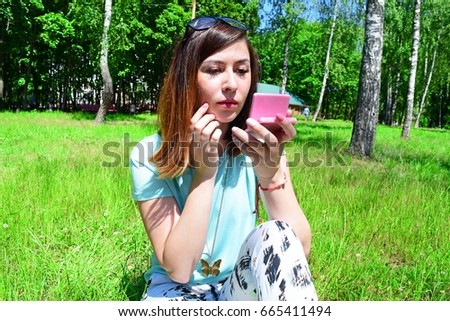 European brunette girl looking in mirror sitting on green grass in park