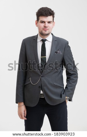 European businessman in triple suit. Handsome man. Euro logo icon pinned to the suit.