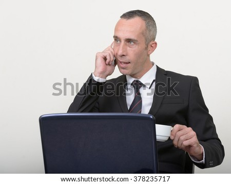 European businessman talking on phone while holding coffee cup and using laptop computer