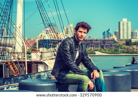 European businessman traveling in New York. Wearing black leather jacket, blue jeans, a young guy with beard, sitting on bench at harbor, frowned, sad, missing family, friends. A boat on background.  - stock photo