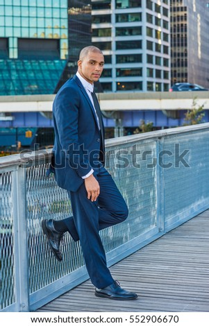European Businessman with shaved head traveling, working in New York, wearing blue suit, white shirt, black tie, standing by fence in business district, taking work break.