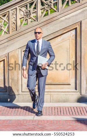 European Businessman with shaved head travels, works in New York, wearing gray suit, tie, leather shoes, sunglasses, holding laptop computer, walking on vintage street under sun. Color filtered effect