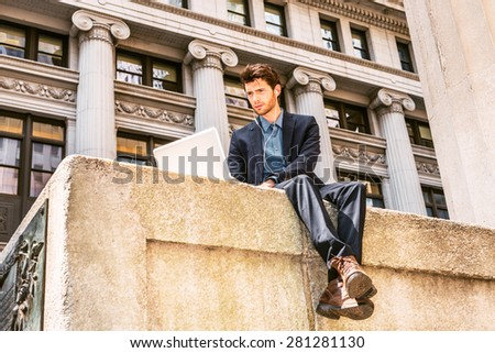 European businessman working on street in New York. Dressing in blue suit, brown leather boot shoes, wearing ear phone, a young guy with beard, reading, typing on laptop computer. Instagram effect. - stock photo