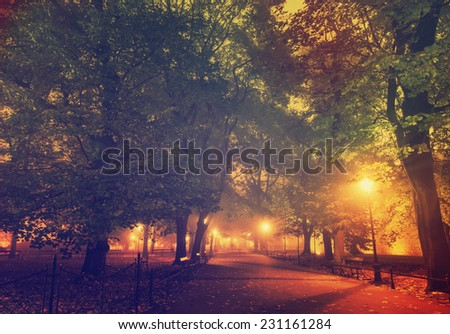 European city park with benches at night in autumn, vintage background - stock photo