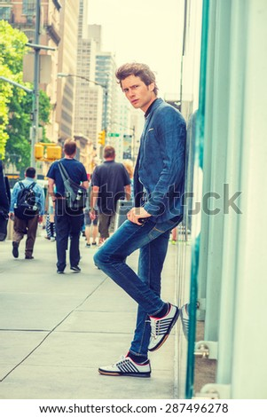 European College Student in New York. Wearing blue blazer, jeans, sneakers, holding laptop computer, a young guy standing against glass wall on street. People walking on background. Instagram effect. - stock photo