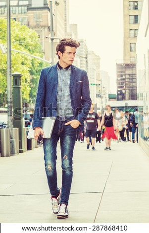 European College Student Studying in New York. Wearing blue blazer, jeans, sneakers, holding laptop computer, a young guy confidently walking on street in sunny afternoon. Instagram filtered effect.