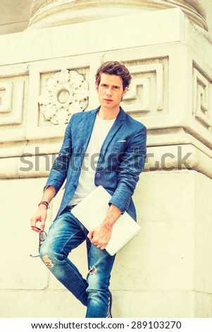 European college student studying in New York. Wearing blue blazer, white under shirt, jeans, holding laptop computer, sunglasses, a young guy standing by column on campus, relaxing. Instagram effect  - stock photo