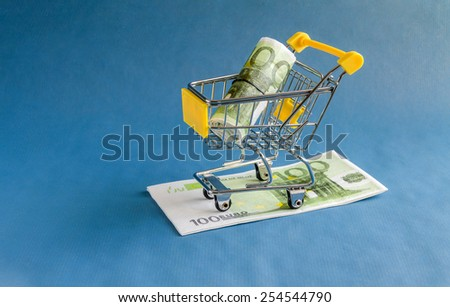 European currency. Hundred Euro in shopping trolleys on a blue background. - stock photo