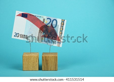 European economy crisis, decline of Euro currency, twenty Euro banknote with red arrow down at wooden metal holders over blue background - stock photo