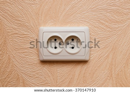 European electric outlet on wall covered with wallpaper - stock photo