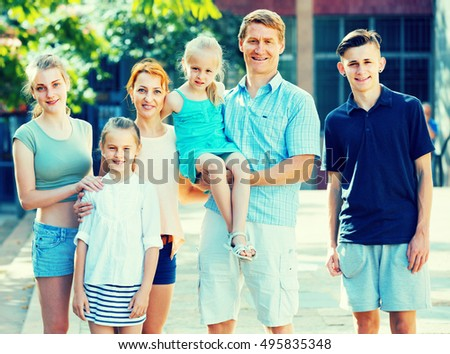 European family of six people happily walking together in summer city