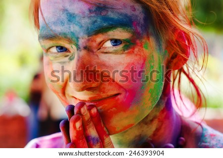 European girl celebrate festival Holi in Delhi, India. The main day, Holi, is celebrated by people throwing coloured powder and coloured water at each other. - stock photo