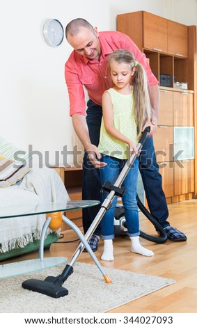 european girl helping father to do regular clean-up indoors