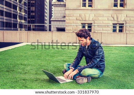 European graduate student studying in New York. Wearing black leather jacket, blue jeans, boot shoes, young guy with beard, crossing legs, sitting on green lawn, reading, working on laptop computer.  - stock photo