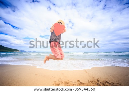 European guy in nice white hat holds hand-made large red heart jumps high over beach against wave surf - stock photo