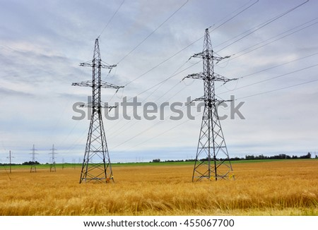 European high voltage lines and power pylons on a background of yellow field. Beautiful agricultural landscape. High-voltage power transmission tower. Energy. Countryside.   - stock photo