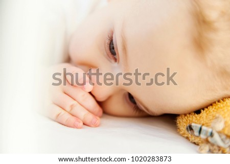 European kid lies in a white crib with a finger in his mouth