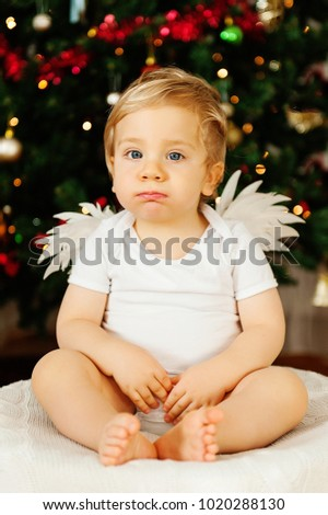 European kid with angel wings sits on the background of a Christmas tree