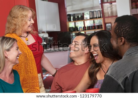 European lady talking with diverse group of people in a bistro