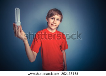 European-looking boy of ten years holding a light bulb on a gray background retro